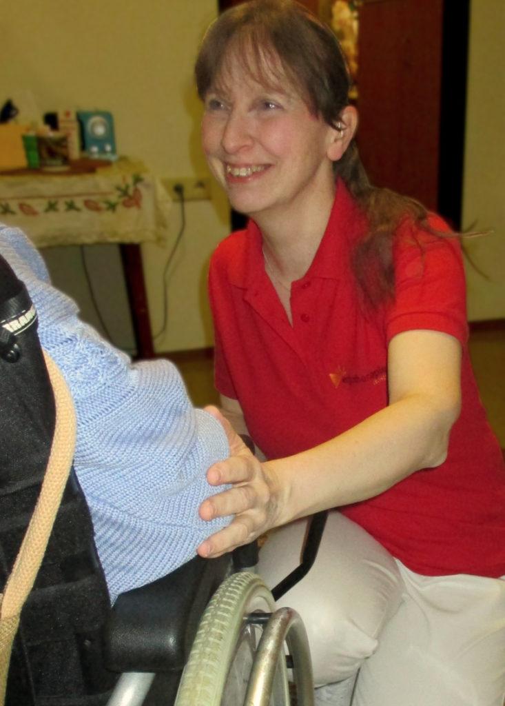 Ergotherapeutin Martina König spricht mit einer Klientin im Rollstuhl